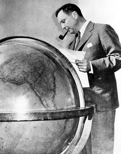 Pan Am's Juan Trippe standing at his Globe