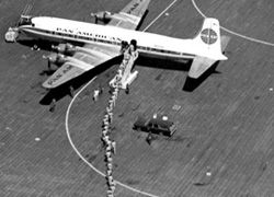 Aerial view of troops boarding Pan Am DC-6, Saigon, Vietnam