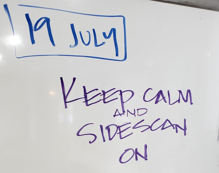 "Whiteboard reads ""Keep Calm and Sidescan On"" Samoan Clipper Search Update 7-19-19 update 2"